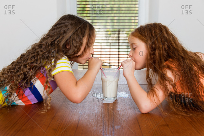 Two little girls sharing a drink