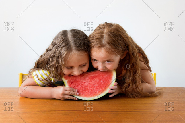 Two little girls sharing a slice of watermelon