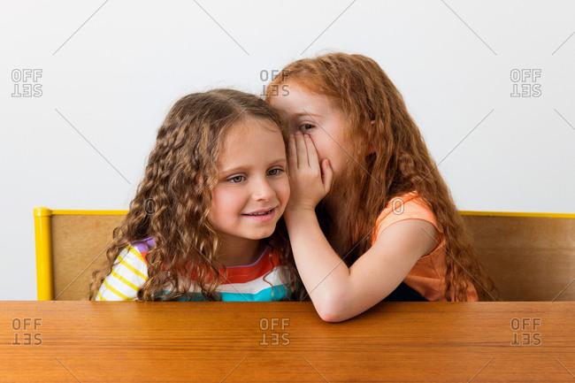 Little girl whispering in her sister's ear