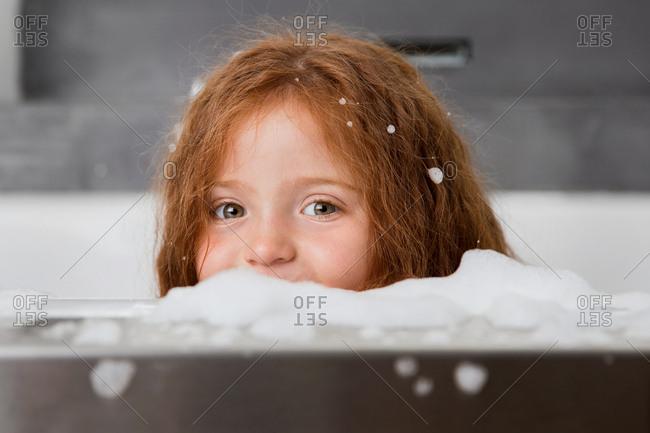 Little girl in a soapy bubble bath