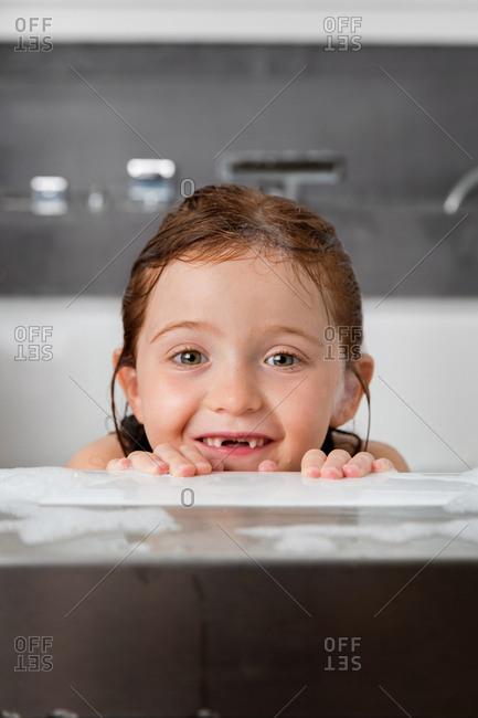 Redhead girl in a soapy bubble bath