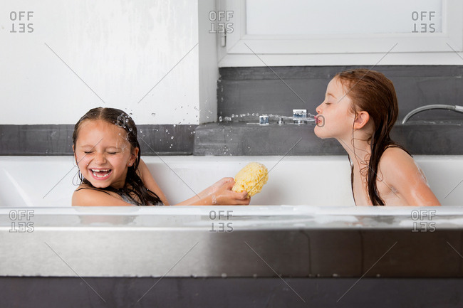 Young girl spitting water at sister in bath