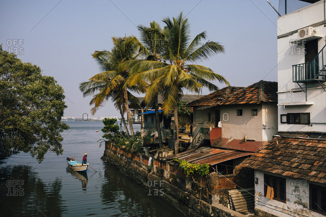 Fort Kochi, India - February 12, 2018: A fishing boat makes its way through a small neighborhood canal in Fort Kochi