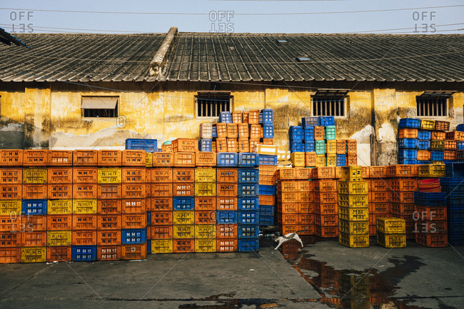 Fort Kochi, India - February 12, 2018: Crates piled against an old warehouse at a fishing dock