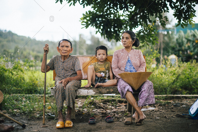 My Lai, Vietnam - October 2, 2017: Three generations of Vietnamese sit on a bench near a rice field where US helicopters and soldiers landed in My Lai on March 16, 1968