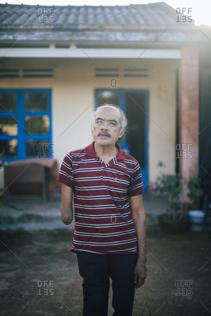 My Lai, Vietnam - October 3, 2017: A portrait of Do Tan Thanh, a survivor of the My Lai Massacre in central Vietnam who lost an eye, arm, and most of his leg on March 16, 1968