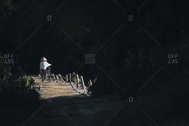 My Lai, Vietnam - October 3, 2017: Locals cross a small wooden foot bridge in Quang Ngai Province in central Vietnam, just downriver from the My Lai Massacre in 1968