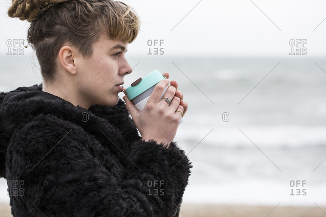 Portrait of young woman with brown hair and dreadlocks and a lip piercing wearing black furry jacket, standing by ocean, holding mug to her lips