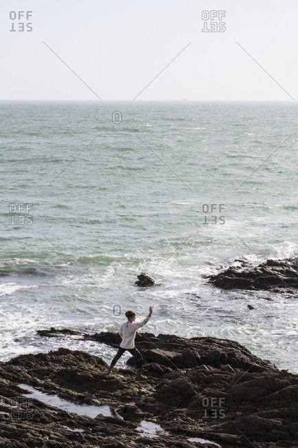 Young woman with brown hair and dreadlocks wearing white blouse standing on rocky shore by ocean, doing Tai Chi
