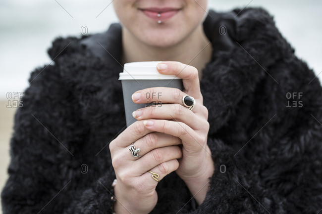 Close up of young woman wearing black furry jacket holding paper cup with hot drink