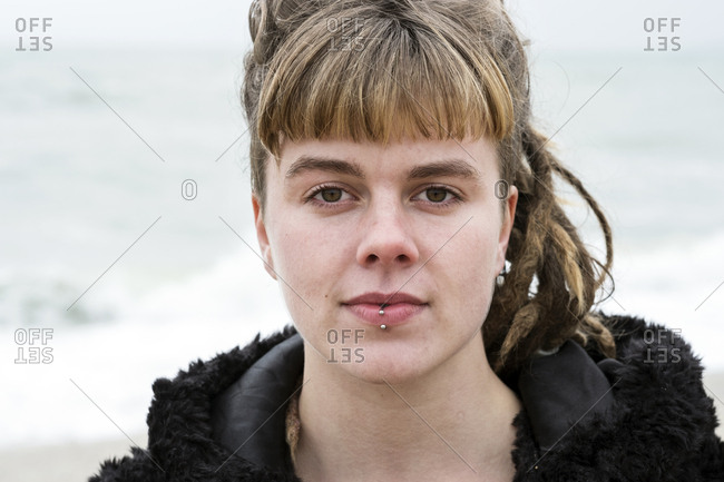 Portrait of young woman with brown hair and dreadlocks and a lip piercing wearing black furry jacket, looking at camera