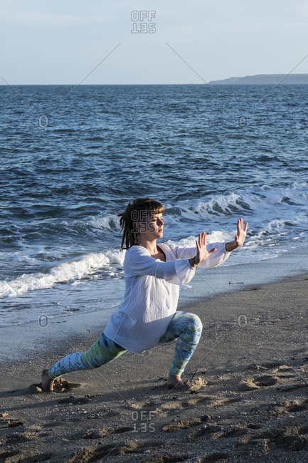 Young woman with brown hair wearing white blouse standing on a beach by the ocean, doing Tai Chi