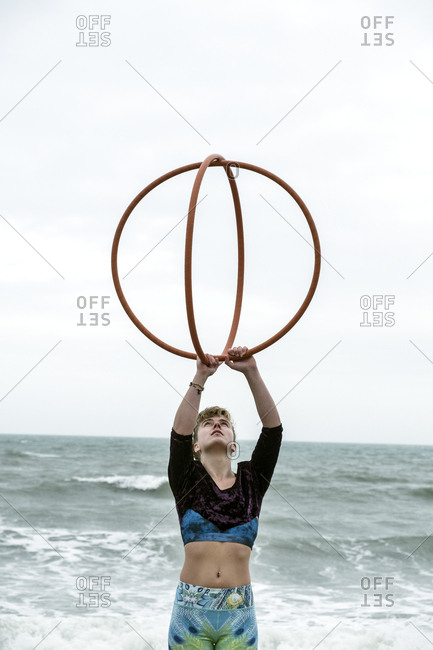 Young woman with brown hair and dreadlocks standing by the ocean, balancing two hula hoops