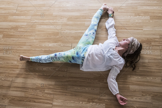 High angle view of young woman wearing headscarf and white blouse lying on her back on hardwood floor, doing yoga