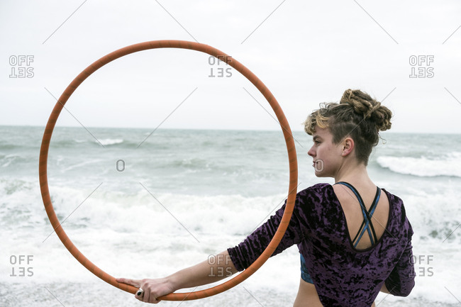 Young woman with brown hair and dreadlocks standing on a sandy beach by the ocean, balancing hula hoop