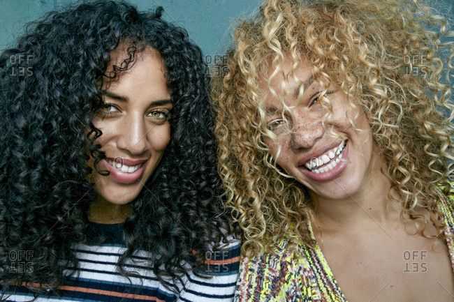 Portrait of two young women with long curly black and blond hair, smiling at camera
