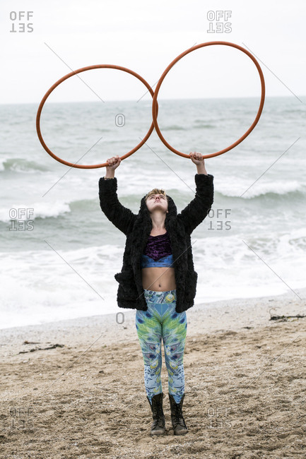 Young woman with brown hair and dreadlocks standing on a sandy beach by the ocean, balancing two hula hoops