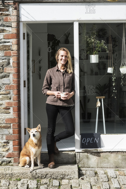 Smiling female owner of plant shop standing outside her store, a dog sitting next to her