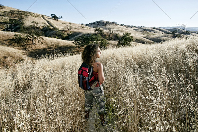 Young woman with curly brown hair hiking in urban park