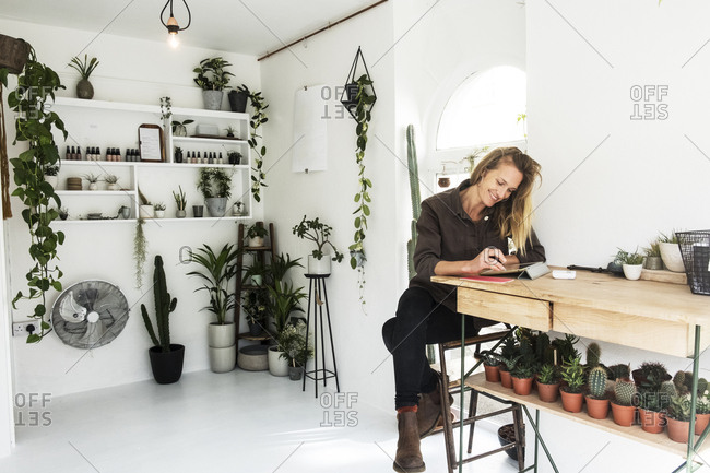 Female owner of plant shop sitting at table, working on digital tablet, a selection of plants on wooden shelves