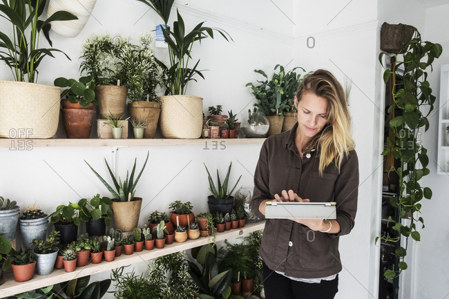 Female owner of plant shop standing next to a selection of plants on wooden shelves, holding digital tablet