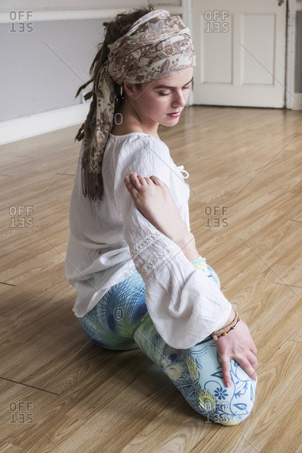 Young woman wearing headscarf and white blouse sitting on floor in yoga pose