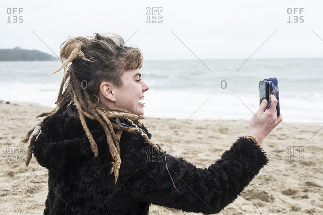Smiling young woman with brown hair and dreadlocks and a lip piercing wearing black furry jacket, sitting on sandy beach by ocean, taking selfie with mobile phone