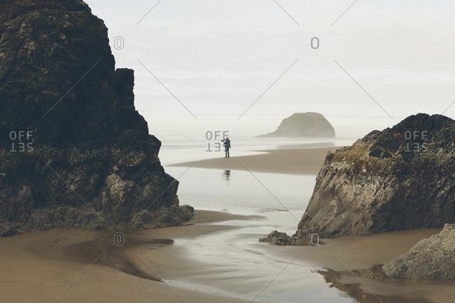 Man taking photos on beach at low tide, Arcadia Beach State Park, Oregon