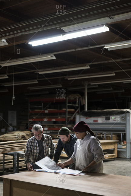 Three mixed race carpenters working on a laptop computer after work hours in a large woodworking factory