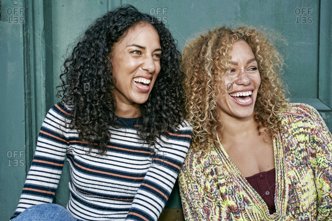 Portrait of two young smiling women with long curly black and blond hair, smiling and laughing