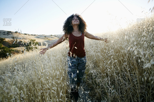 Young woman with curly brown hair hiking in urban park, standing in field, eyes closed