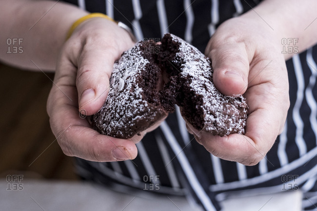 A cook in an apron holding a dark chocolate brownie cake broken in half