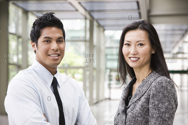Portrait of an Asian businesswoman and a businessman in the lobby of a convention centre