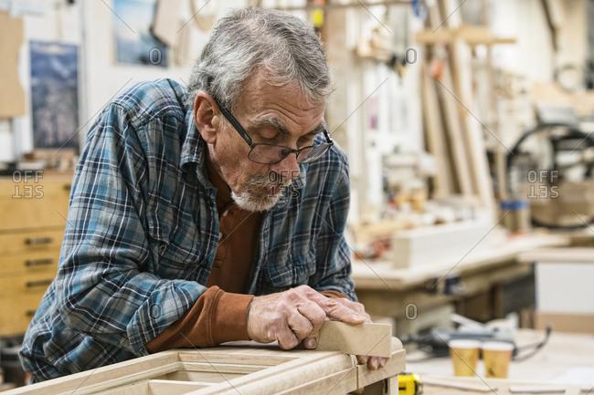 Senior Caucasian  carpenter sanding a wooden cabinet part in a large woodworking shop