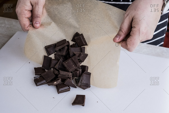 A cook with weighed chocolate pieces on greaseproof paper