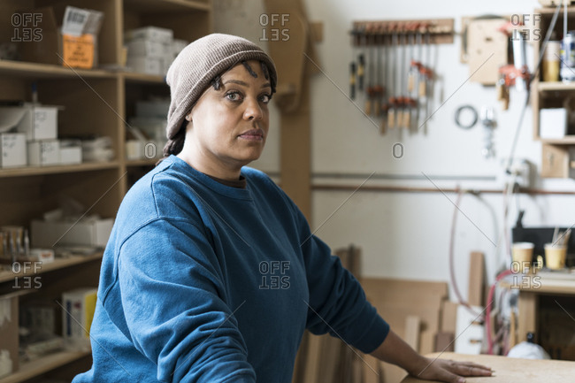 Portrait of a Black woman carpenter in a large woodworking shop