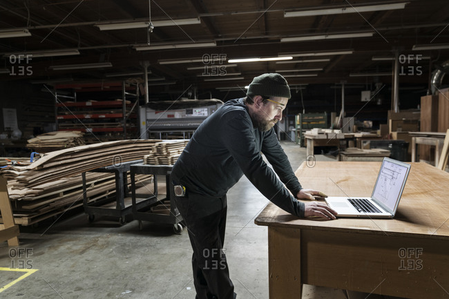 A Caucasian carpenter working on his lap top after hours in a large woodworking factory