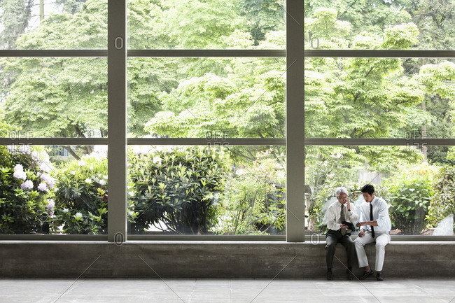 Two businessmen working on a notebook computer and sitting in front of a large window in the lobby of a convention centre