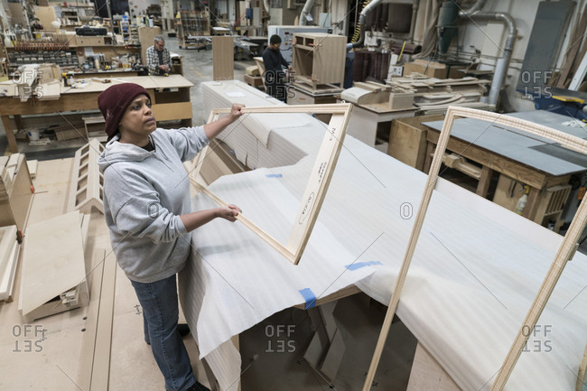 A Black woman carpenter working on a cabinet project in a large woodworking shop
