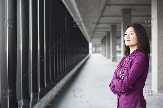 An Asian female business owner in a new raw business space