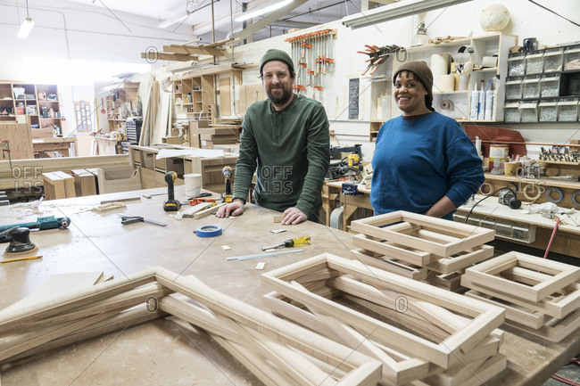 Portrait of a team of two mixed race male and female carpenters in a large woodworking factory