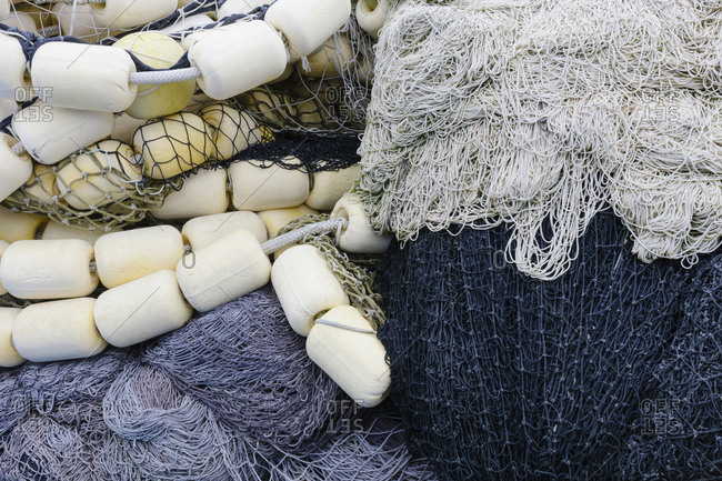 Fishing nets and floats, commercial fishing equipment in a heap on a quayside