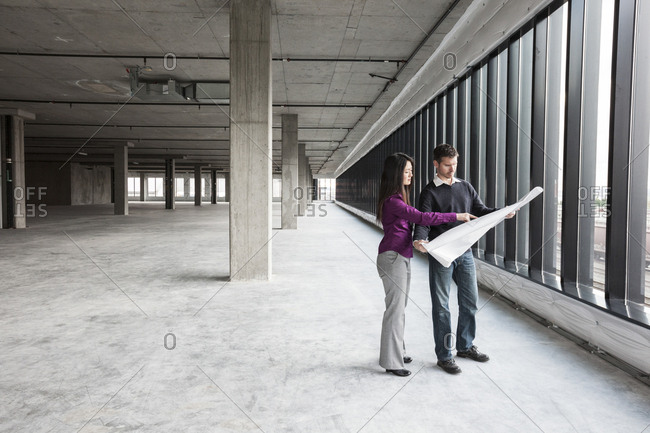 Two architects working on business plans in a new raw business space