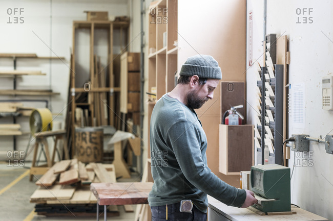 A Caucasian carpenter checking in with a time clock in a woodworking factory