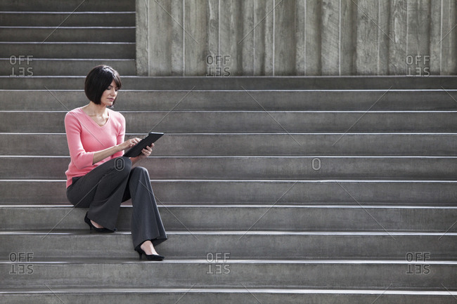 Hispanic businesswoman working on a notebook computer while sitting on steps in a convention centre