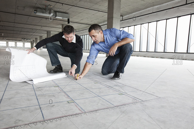 An architect and a business owner crouching over architectural plans and drawing on a concrete floor, planning a new office space in an empty raw built space