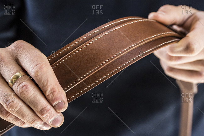 Close up of person holding handmade brown leather camera strap