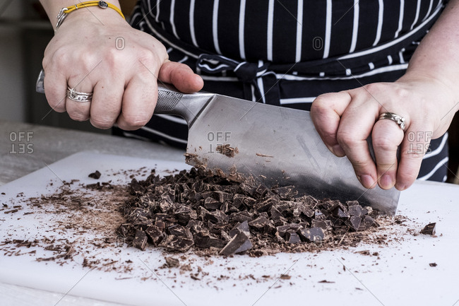 A cook chopping chocolate pieces with a large cleaver