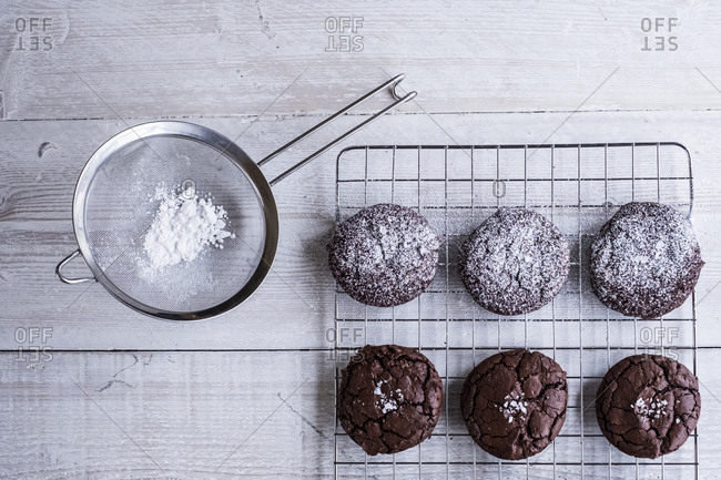 A tray of cooling chocolate brownies, and a sieve with icing sugar for decoration