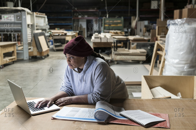 A Black female carpenter working on a lap top computer after work hours in a large woodworking factory
